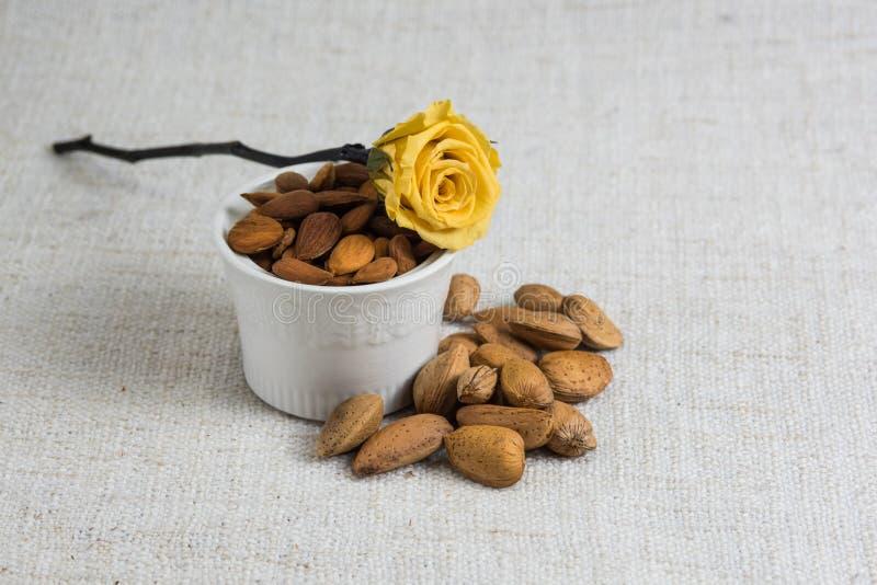 Amandes ?pluch?es dans une cuvette et des fruits secs blancs d'amandes sur la texture beige de tissu, d?coration jaune de fleur,  photographie stock