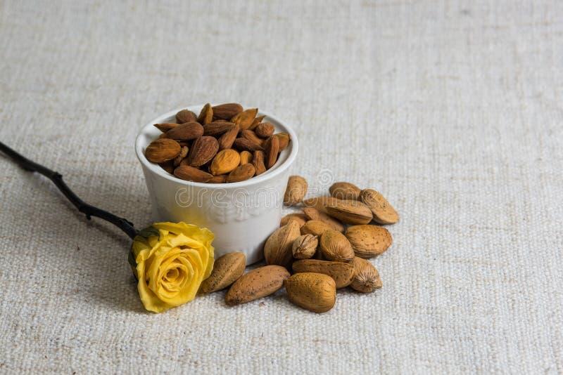 Amandes ?pluch?es dans une cuvette et des fruits secs blancs d'amandes sur la texture beige de tissu, d?coration jaune de fleur,  photo libre de droits
