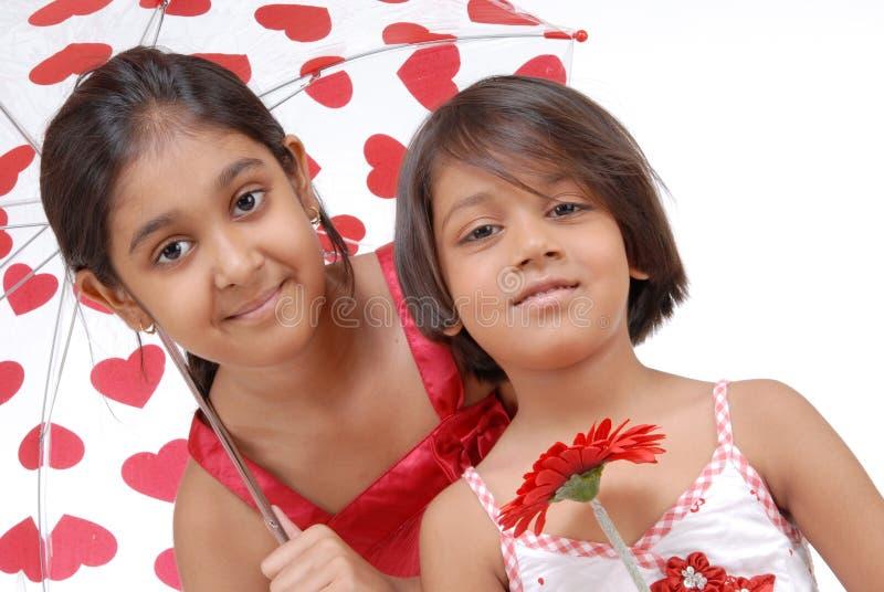 Amando duas irmãs no tema vermelho e branco fotos de stock