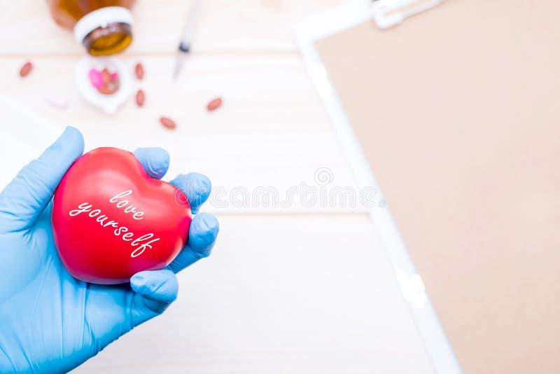 Amando y tome el cuidado de sí mismo entonces comprueban su cuerpo y enfermedad cardíaca fotografía de archivo