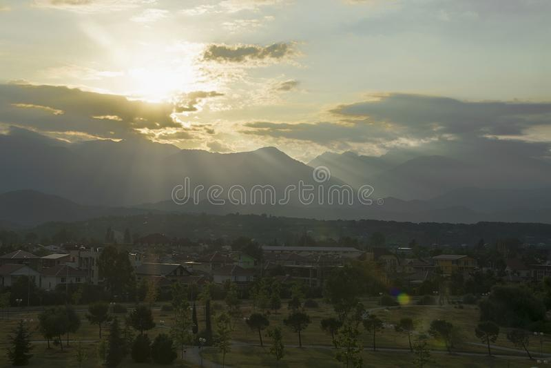 Amanece el sol de detrás las montañas una hermosa vista del pueblo del verano de las palmeras fotografía de archivo