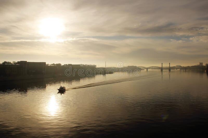 Amanecer brumoso sobre la ciudad y el río imagenes de archivo
