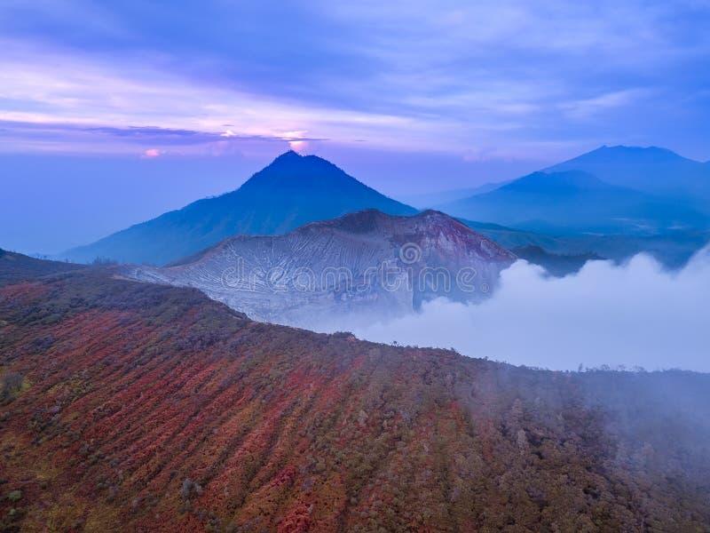Amanecer en las cuestas de Volcano Ijen Silueta del hombre de negocios Cowering fotos de archivo libres de regalías