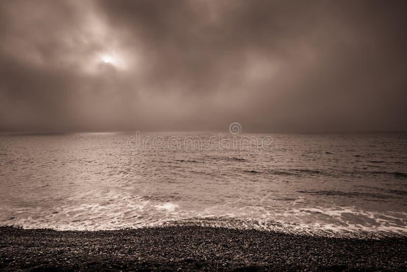 Amanecer oscuro y nublado en la playa fotografía de archivo