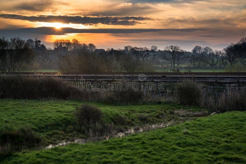 Amanecer sobre pistas ferroviarias con paisaje del campo fotos de archivo libres de regalías