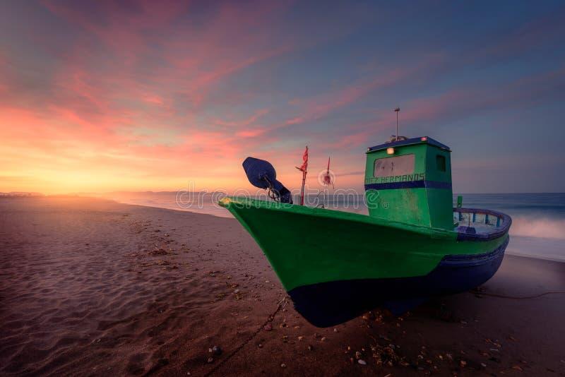Amanezca detrás de un barco situado en la orilla de la playa imagen de archivo libre de regalías
