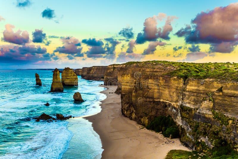 Amanhecer na costa do oceano as nuvens que giraram cor-de-rosa no alvorecer sobre as rochas conhecidas doze apóstolos Curso foto de stock royalty free