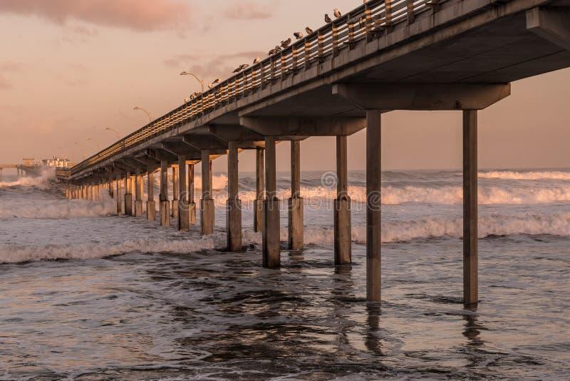 Amanhecer no cais da pesca da praia do oceano fotografia de stock royalty free