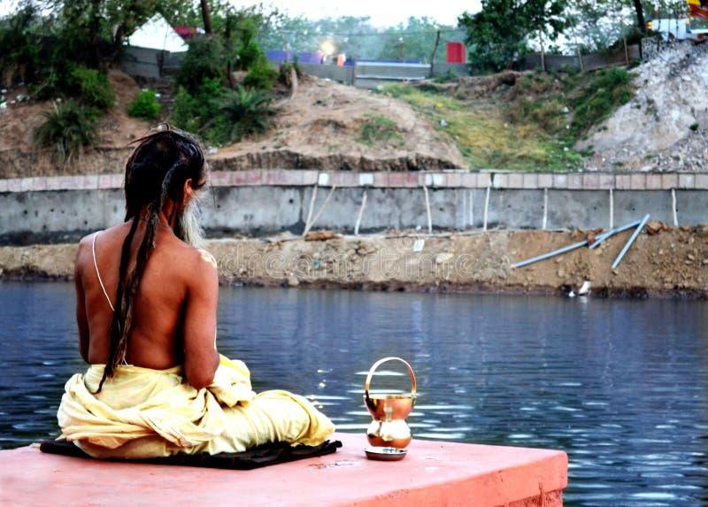 Amanhecer um sadhu que medita sobre o banco do rio do kshipra no grande mela do kumbh, Ujjain, Índia imagens de stock royalty free