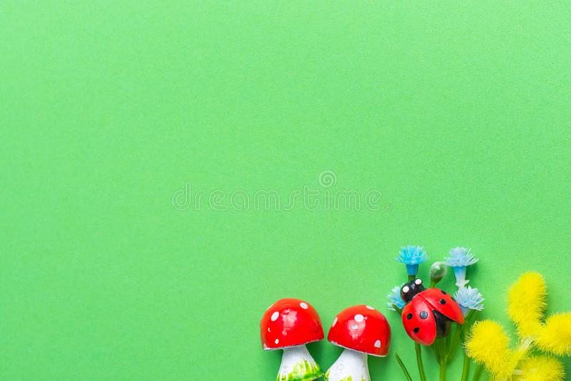 Amanita Mushrooms Small Blue Forget Me Not Yellow Mimosa Flowers Ladybird on Green Background Imitating Grass Greenery. Composition from Small Miniature Kids stock photo