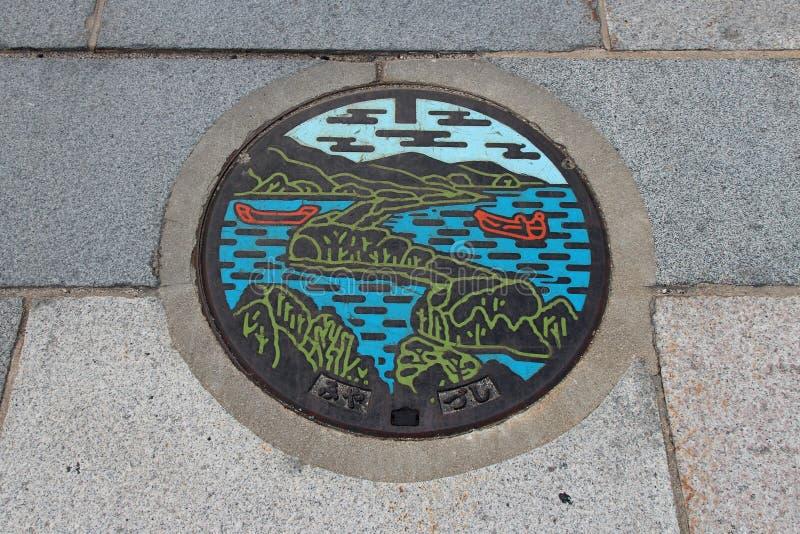 Amano-Hashidate - Japan. A landscape decorates a manhole cover in a street of Amano-Hashidate (Japan). Un paysage décore une plaque d'égout dans une rue stock image