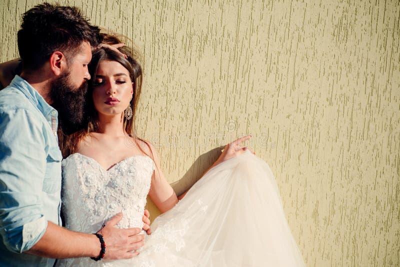 Amano il modo ed il fascino amore delle coppie romantico Sposa sensuale in vestito da sposa bianco Sposo barbuto in casuale immagini stock