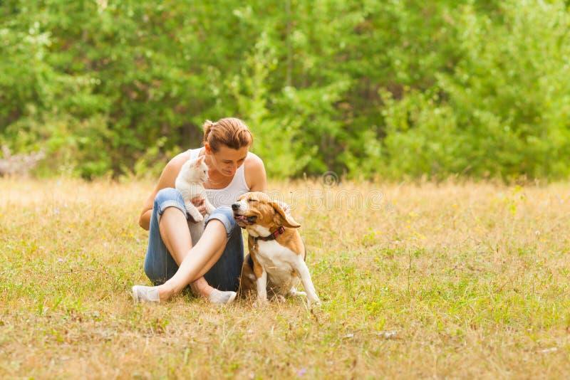 Amante animal da mulher animal do amante que senta-se na grama com seus animais de estimação fotos de stock