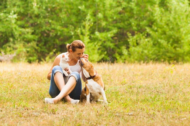 Amante animal que senta-se fora com seus animais de estimação fotografia de stock