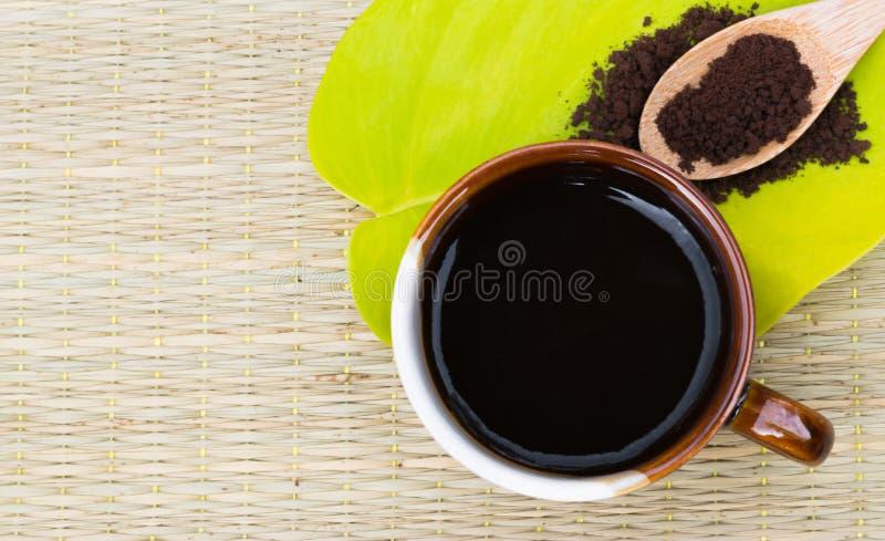 Amante del café La taza de café en la hoja verde con café asado encendido corteja foto de archivo