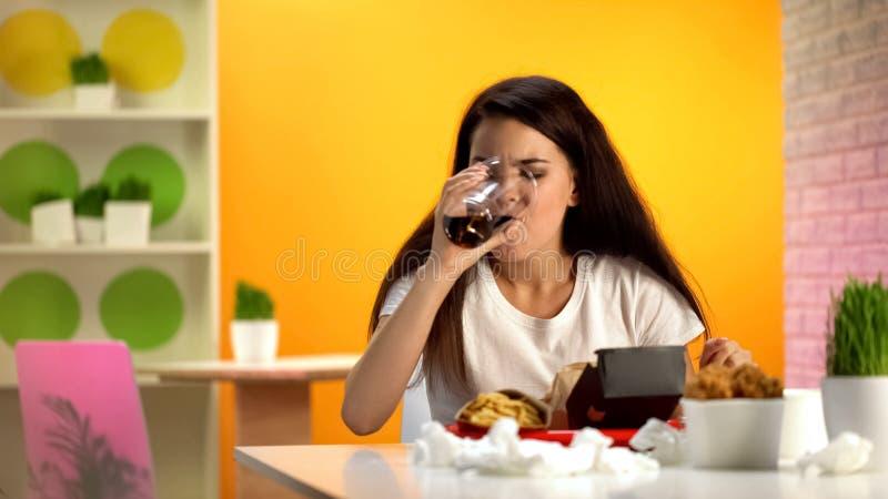 Amante do fast food que bebe a soda doce, batatas fritas, hamburguer, asas fritadas na tabela fotografia de stock royalty free