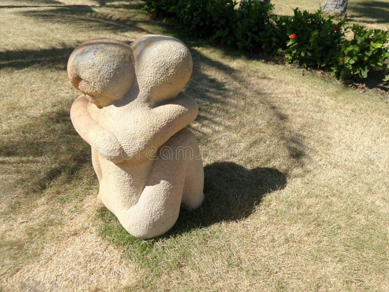 Amante en escultura de la piedra del control en césped verde fotografía de archivo libre de regalías