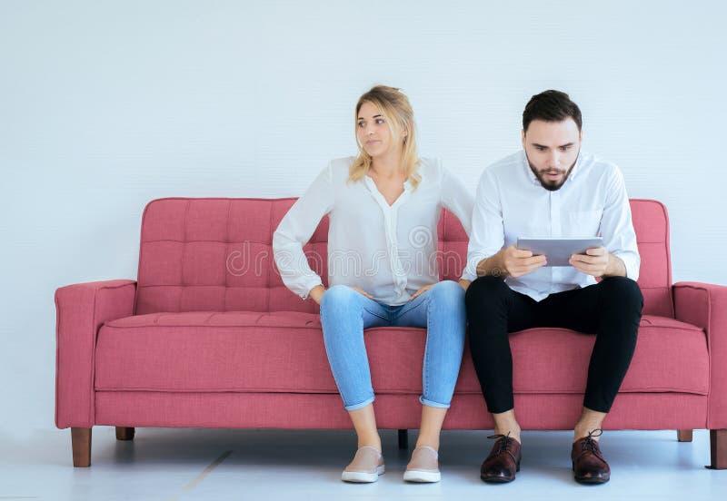 Amante furado e da negligência dos pares que senta-se no sofá em casa junto, edições de família fotografia de stock royalty free