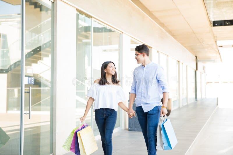 Amantes adolescentes de sorriso na viagem da compra na alameda imagens de stock