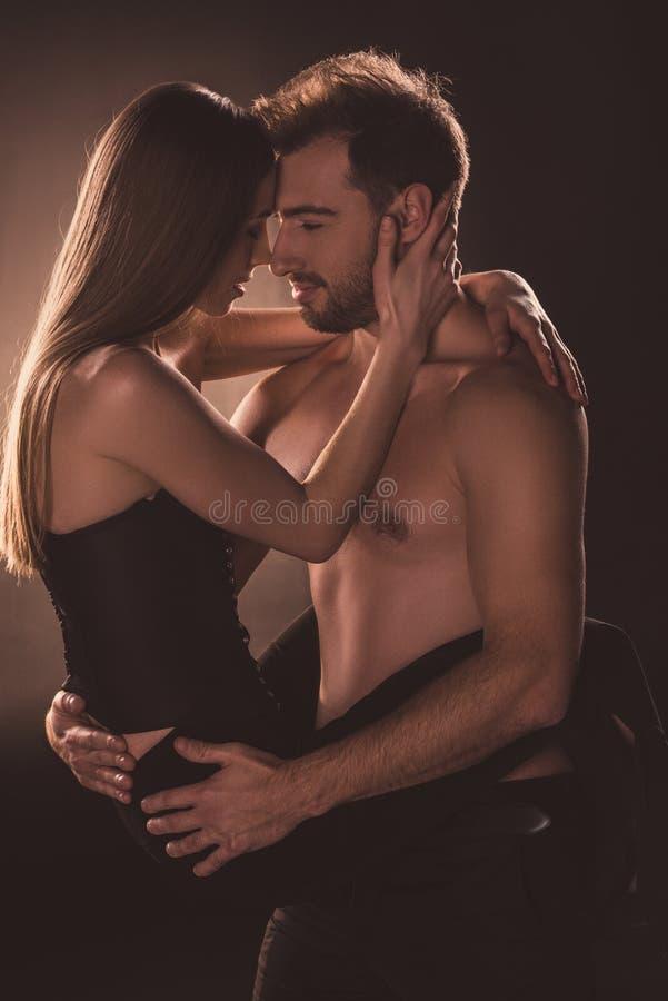 amantes apasionados que abrazan y que miran uno a, imagen de archivo