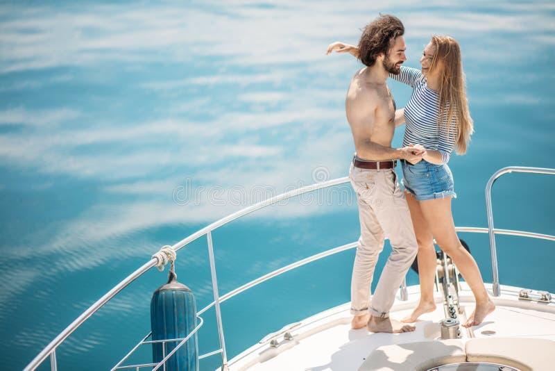 Amantes apasionados que bailan en el arco de la cubierta mientras que navega en el yate foto de archivo