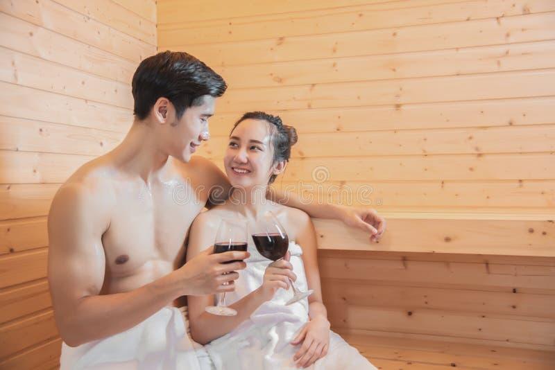 Amantes asiáticos que beben el vino en el sitio de la sauna, tratamiento térmico con vapor, día de fiesta y relajar concepto foto de archivo libre de regalías