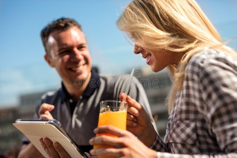 Amantes bonitos novos dos pares no café usando a tabuleta fotografia de stock royalty free