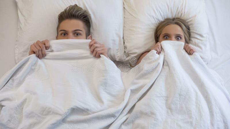 Amantes cogidos en cama por los padres, desconcertados y asustados, pareciendo chocados imagen de archivo