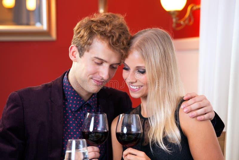 Amantes consideravelmente doces que guardam o vidro dos vinhos fotografia de stock royalty free