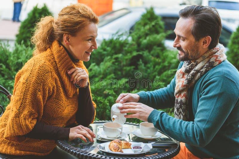 Amantes de meia idade alegres que bebem a bebida quente imagens de stock royalty free