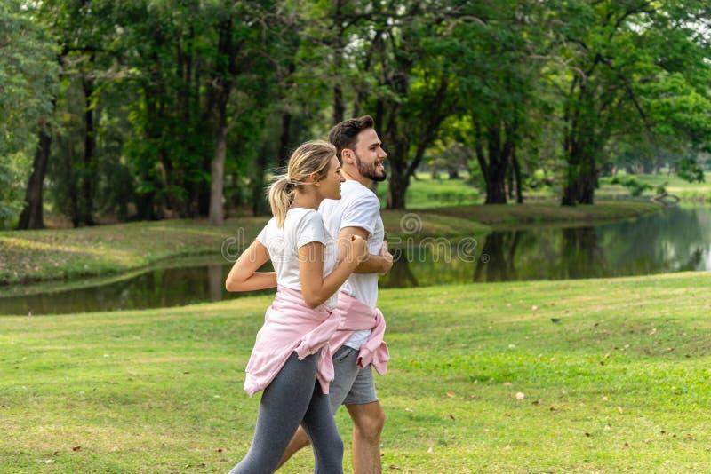 Amantes del hombre y de la mujer que corren en el parque público imágenes de archivo libres de regalías