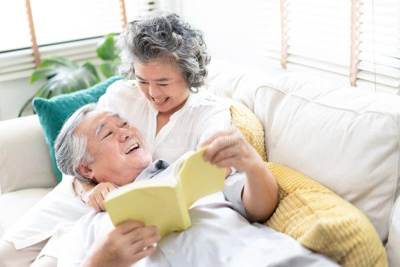 Amantes em uma sala de visitas Pares superiores felizes que relaxam junto em casa com o marido que encontra-se no regaço de sua e fotos de stock