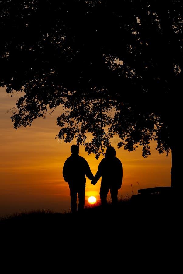 Amantes en el retrato de la puesta del sol fotografía de archivo libre de regalías