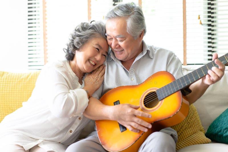 Amantes en una sala de estar Mujer mayor feliz que abraza al hombre barbudo i fotografía de archivo