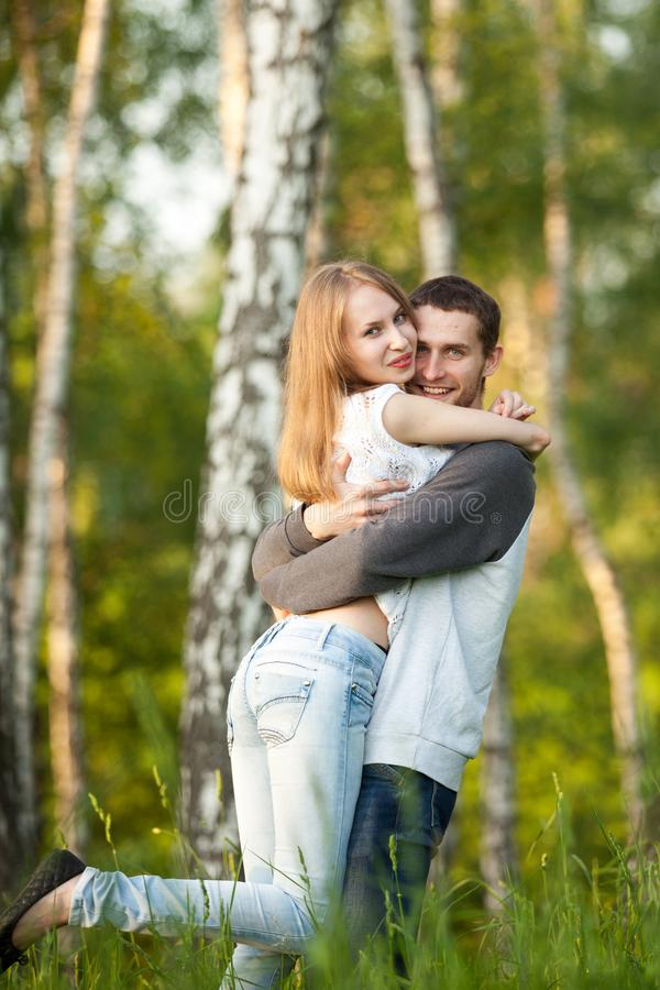 Amantes felices que abrazan en la arboleda del abedul fotos de archivo