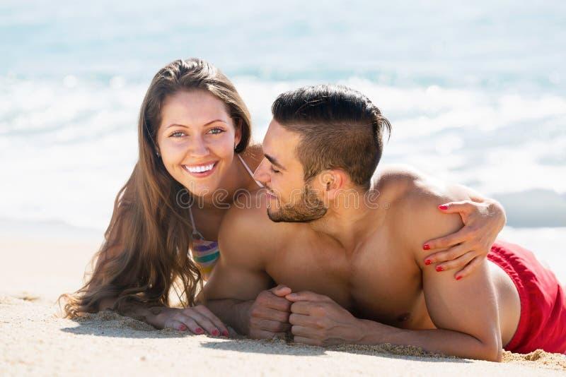 Amantes felices que descansan sobre la playa arenosa imagenes de archivo