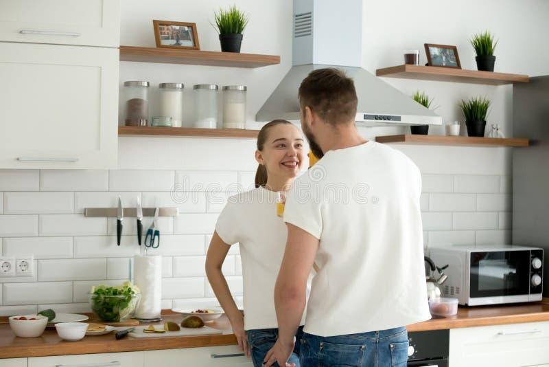 Amantes felices que miran en los ojos que disfrutan de la intimidad que cocina el desayuno imágenes de archivo libres de regalías