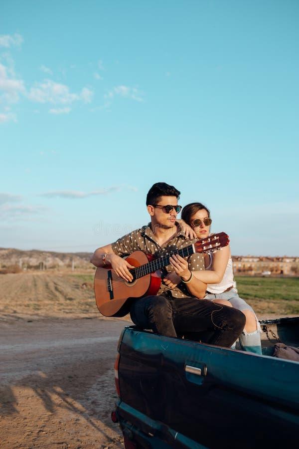 Amantes jovenes de los viajeros que se divierten que toca la guitarra encima del coche del jeep 4x4 Junte la fabricación de vacac foto de archivo