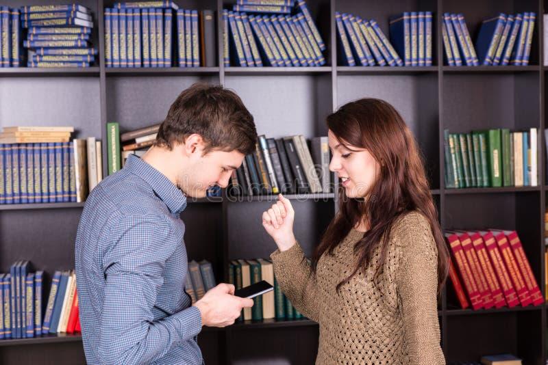 Amantes jovenes que miran el teléfono móvil junto fotos de archivo