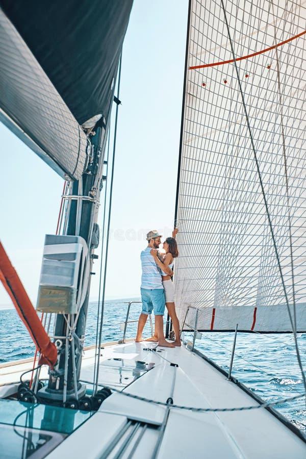 Amantes jovenes que pasan tiempo feliz en un yate en el mar imagen de archivo