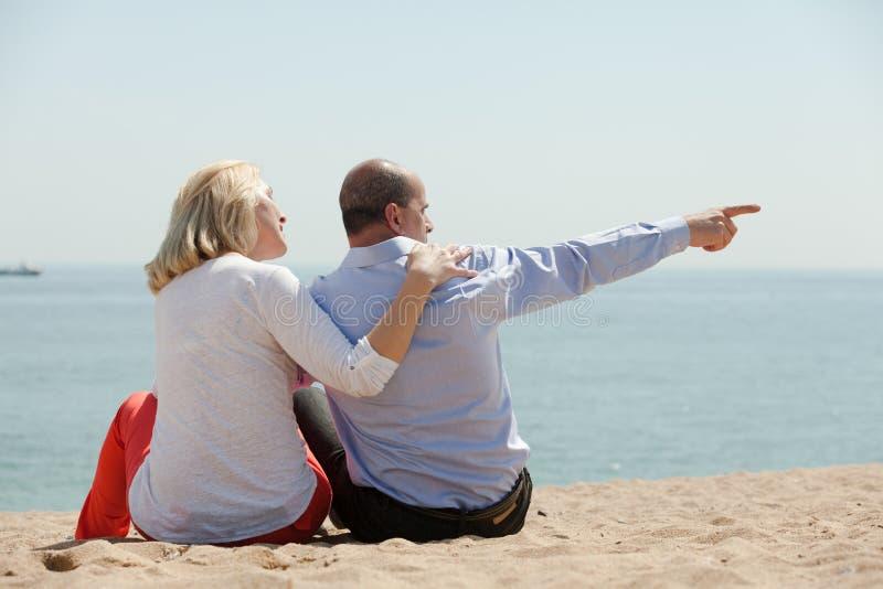 Amantes maduros que se sientan en la playa foto de archivo libre de regalías