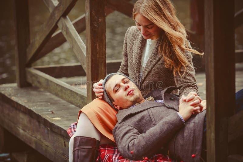 Amantes mulher e homem que sentam-se perto do lago fotografia de stock royalty free