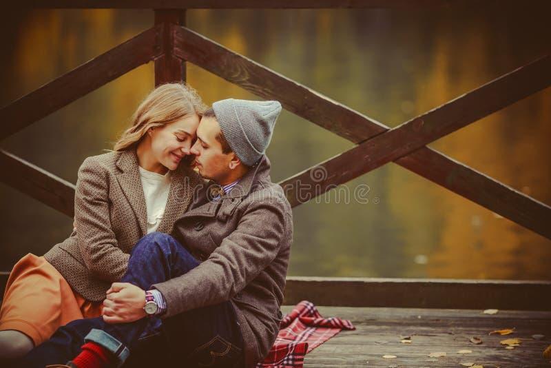 Amantes mulher e homem que sentam-se perto do lago fotografia de stock