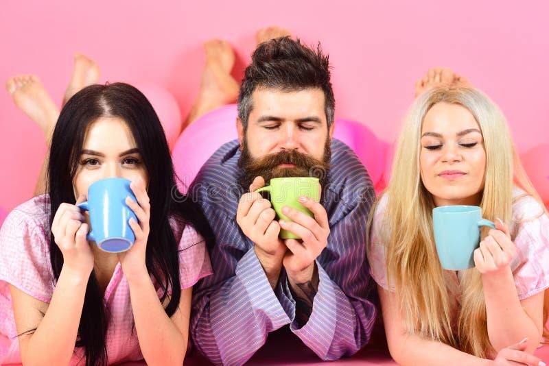 Amantes no café da bebida do amor na cama O Threesome relaxa na manhã com café Conceito dos amantes Homem e mulheres em doméstico imagens de stock royalty free