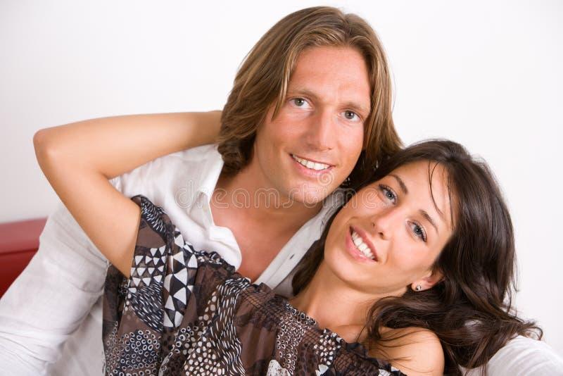 Amantes novos abraçados no sofá imagens de stock