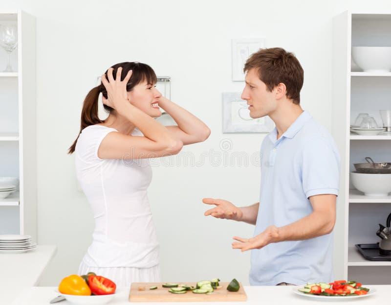 Amantes novos que têm a disputa na cozinha imagem de stock royalty free