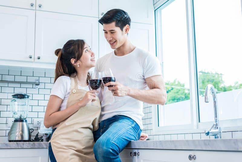 Amantes o pares asi?ticos que beben el vino en sitio de la cocina en casa Luna de miel del concepto del amor y de la felicidad y  imagen de archivo