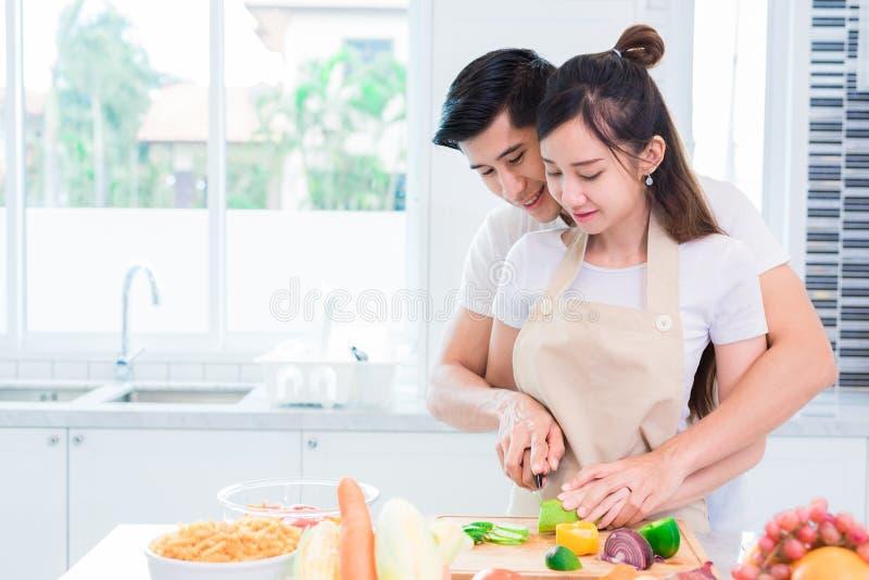 Amantes o pares asi?ticos que cocinan y que cortan la verdura en sitio de la cocina Hombre y mujer que se miran en hogar D?a de f imagen de archivo libre de regalías