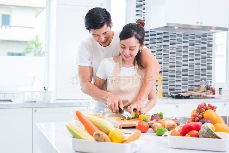 Amantes o pares asi?ticos que cocinan y que cortan la verdura en sitio de la cocina Hombre y mujer que se miran en hogar D?a de f fotos de archivo