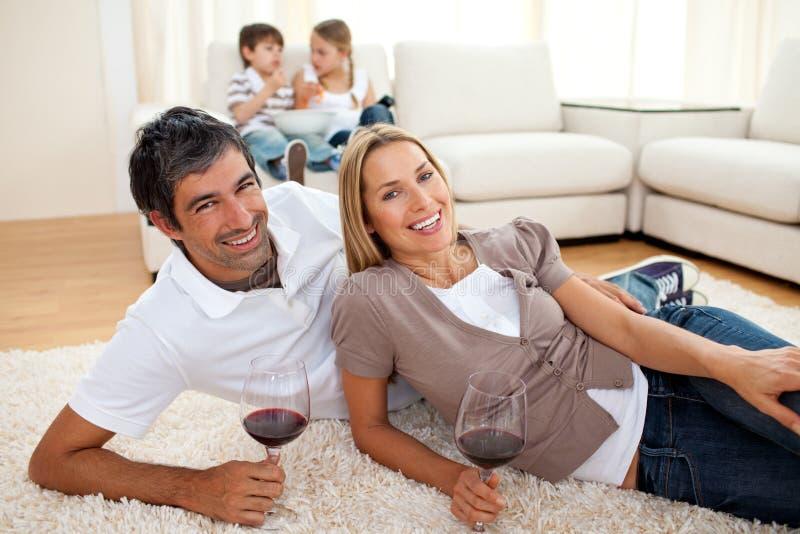 Download Amantes Que Bebem O Vinho Que Encontra-se No Assoalho Imagem de Stock - Imagem de lifestyle, conforto: 12813585